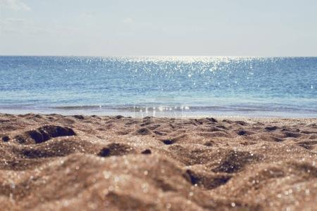 Yellow sand on beach and glare of sun against sea