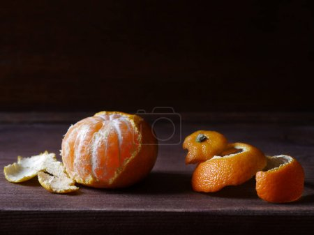 Half-peeled mandarin and peel on wooden surface, minimalistic still life