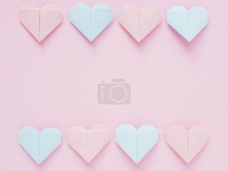 Pattern of paper origami hearts on pink background