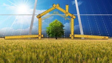 Foto de Regla de madera en forma de casa ecológica con los paneles solares en el campo. Concepto de proyecto de casa ecológica - Imagen libre de derechos