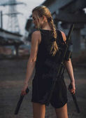 Cosplayer  girl with machine gun behind back and pistols in cost