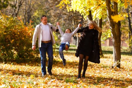 Photo for The family walks in the park in autumn - Royalty Free Image