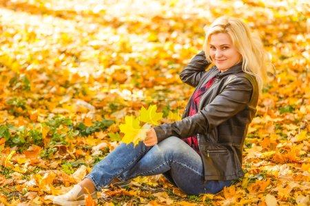 Photo pour Fille assise dans le parc d'automne - image libre de droit