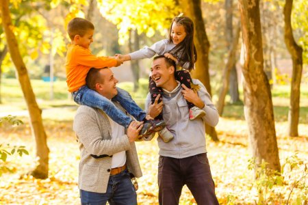 Photo for Happy fathers and children having fun outdoors in orchard garden, playing together - Royalty Free Image
