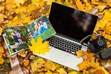 Photo for Photobook autumn leaves and laptop - Royalty Free Image