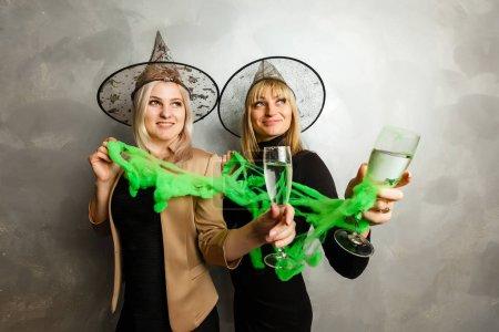 Photo pour Portrait de deux jeunes femmes heureuses en costumes d'Halloween sorcière noire - image libre de droit