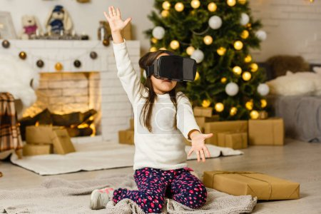 Photo for Portrait of little girl playing in virtual reality headset at home - Royalty Free Image