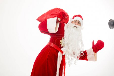 Photo for Man in Santa claus costume holding a red sack with presents - Royalty Free Image