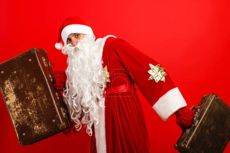 Photo for Santa Claus Standing With Travel Bag with Gits on red background - Royalty Free Image