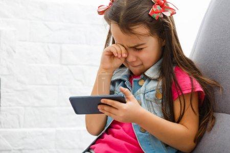 Photo pour Petite fille pleurait et maintenant smartphone. La petite fille cacha son visage et s'écria, tenant un téléphone portable dans ses mains. - image libre de droit