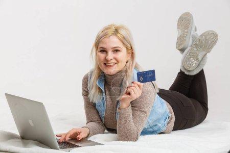 Photo pour Une femme heureuse, tenant une carte de crédit et le shopping sur internet - image libre de droit