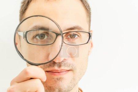 Photo pour Homme regardant à travers une loupe isolée sur fond blanc - image libre de droit