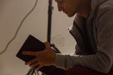 Photo pour Jeune homme religieux priant Dieu sur fond sombre, effet noir et blanc - image libre de droit