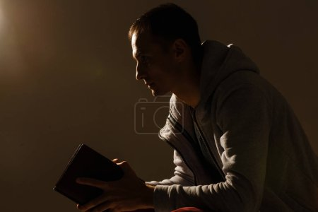 Photo pour Handsome man sit prayer on black background. His hands are praying for God's blessings. - image libre de droit