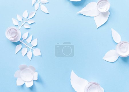 frame with white paper flowers on blue background. Cut from paper.