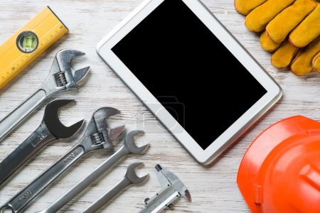 Photo for Set of industrial tools and tablet on wooden surface. Make online service order concept - Royalty Free Image