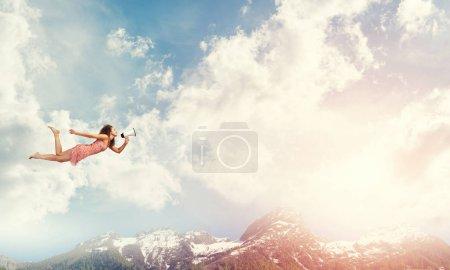 Foto de Mujer joven con megáfono volando alto en el cielo - Imagen libre de derechos