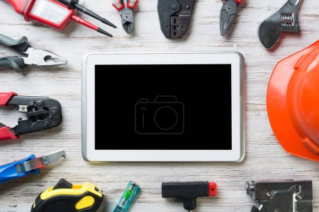 Photo for Set of industrial tools and tablet on wooden surface - Royalty Free Image