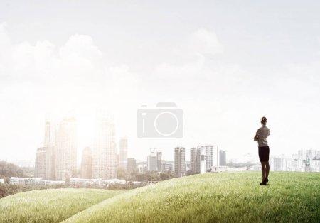 Foto de Elegante mujer de negocios de pie en la colina verde y mirando hacia el futuro. Alcanzar la parte superior del concepto de éxito - Imagen libre de derechos