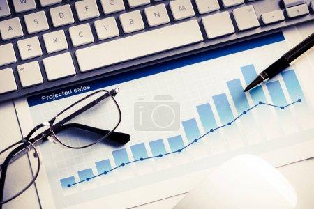 Photo pour Lieu de travail avec souris clavier et papiers avec graphiques et diagrammes - image libre de droit