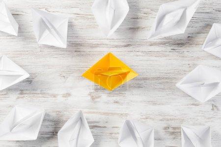 Photo pour Ensemble de bateaux origami sur table en bois. Concept de leadership d'entreprise - image libre de droit