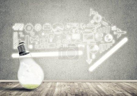 Foto de Bombilla de luz brillante de vidrio y negocios esbozó ideas en la pared. Ideas de marketing eficaces - Imagen libre de derechos