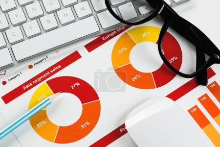 Photo pour Lieu de travail avec lunettes à clavier et documents financiers sur la table - image libre de droit