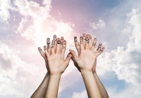 Photo pour Mains de l'homme et de la femme sur fond de nuages représentant l'amour et le bonheur. Heureux d'être ensemble concept - image libre de droit