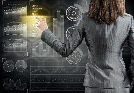 Photo pour Vue arrière de femme d'affaires travaillant avec l'interface de panneau virtuel. Femme d'affaires debout avec le dos et appuyant sur l'icône sur l'écran des médias - image libre de droit