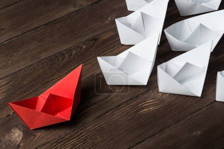 Foto de Conjunto de barcos de origami en mesa de madera. Concepto de liderazgo empresarial - Imagen libre de derechos