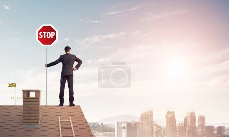 Businessman standing on house roof and holding sto...