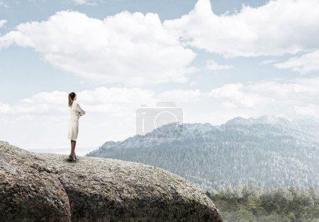 Foto de Elegante mujer de negocios de pie en la parte superior de la roca y mirando hacia el futuro. Alcanzar la cima del éxito - Imagen libre de derechos