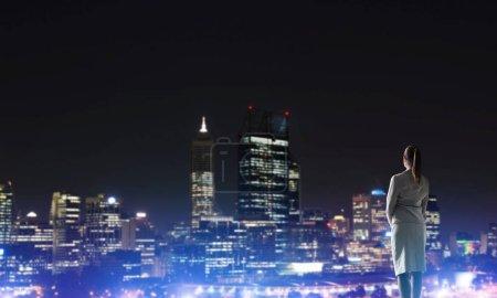 Woman looking at night city