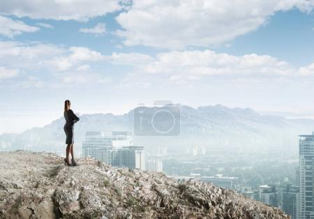 Businesswoman standing on top of hill