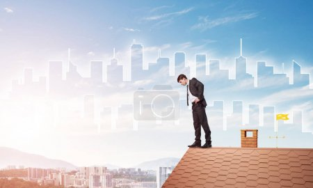 Photo for Young businessman standing on edge of house brick roof and looking down. Mixed media - Royalty Free Image