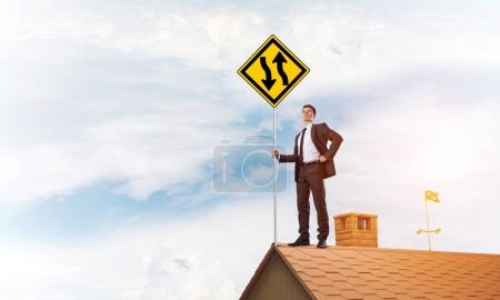 Businessman showing yellow roadsign