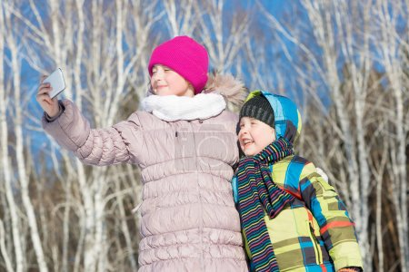Photo for Winter activity concept. Two happy kids making selfie photo in winter park - Royalty Free Image