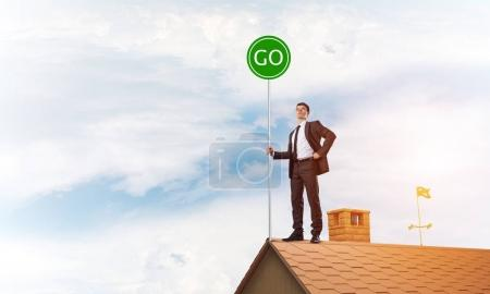 businessman standing on house roof