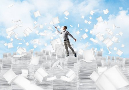 Man in casual wear keeping hand with book up while standing among flying books with cityscape on background