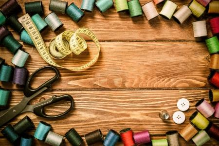 Photo for Bright image of sewing kit accessories on wooden table - Royalty Free Image