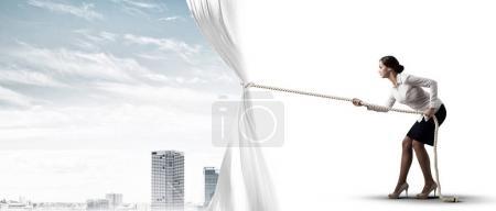 Businesswoman pulling white blank fabric