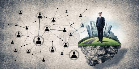 Elegant businessman on flying green island against concrete background, Concept of modern wireless technologies