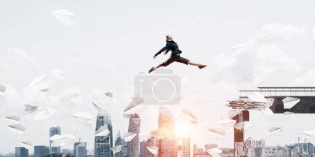 Businesswoman jumping over gap with flying paper planes in concrete bridge as symbol of overcoming challenges. Cityscape and sunlight on background. 3D rendering.