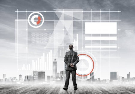 Back view of young businessman looking at cityscape with business icons and chart