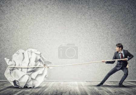 Man pulling with effort big crumpled ball
