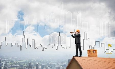 businessman in suit and helmet on roof