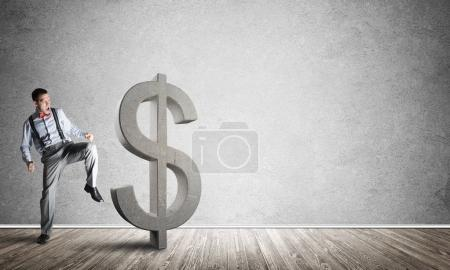 Determined banker man in empty concrete room breaking dollar figure