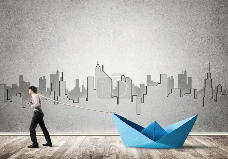 Photo for Successful businessman pulling with rope paper boat - Royalty Free Image