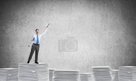 Photo pour Homme d'affaires tenant la main avec le livre vers le haut tout en se tenant sur une pile de documents papier avec fond gris. Techniques mixtes . - image libre de droit