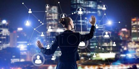 Photo pour Vue arrière de la femme d'affaires contre le paysage urbain nocturne travaillant avec le concept de médias de connexion sociale - image libre de droit